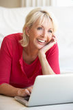 Middle age woman on her laptop computer. At home Stock Image