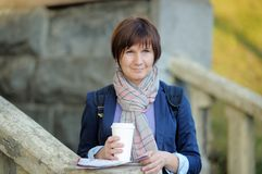Middle age woman holding paper cup and map Stock Images