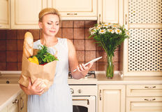 Middle age woman in the kitchen with paper shopping bag full of. Vegetables and bread checking with chopping list on tablet pc Royalty Free Stock Photo