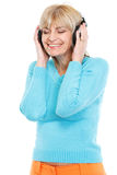 Middle age woman listening music in headphones Stock Images