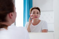 Free Middle Age Woman Looking In Mirror On Face. Wrinkles And Anti Aging Skin Care Concept. Selective Focus Royalty Free Stock Photography - 128238727