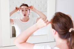 Middle age woman looking in mirror on face wrinkle forehead in bedroom. Wrinkles and anti aging skin care concept. Selective focus.  stock photos