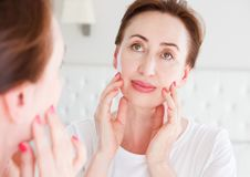 Middle age woman looking in mirror on wrinkle face on forehead. Menopause, Wrinkles and anti aging skin care concept. Selective. Focus royalty free stock photos