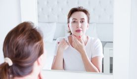 Middle age woman looking in mirror on wrinkle face on forehead. Menopause, Wrinkles and anti aging skin care concept. Selective. Focus. Banner stock image