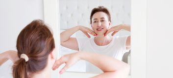 Middle age woman looking in mirror on wrinkle face on forehead. Menopause, Wrinkles and anti aging skin care concept. Selective. Focus. Banner royalty free stock image