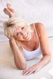 Middle age woman lying down strikes a pose Stock Photos