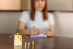 Middle age Woman With Model House from Israel Currencies New Israeli Shekel. stock image