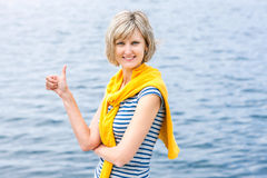 Middle age woman outdoors gesturing thumb up Stock Images