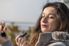 Middle age woman portrait, doing make up under sun light Stock Photos