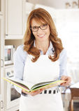 Middle age woman portrait at kitchen Stock Images