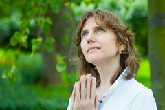 Middle age woman portrait. Smiling middle age woman praying in a park Stock Photo