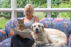 Middle age woman is reading a book with pets together Royalty Free Stock Photo