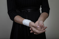Middle age woman showing her bandaged wrist. Middle age woman showing the scars of self harm Stock Photography