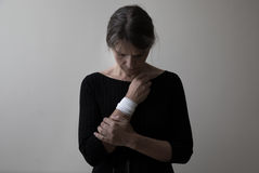 Middle age woman showing her bandaged wrist. Royalty Free Stock Photography