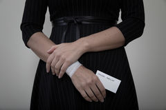 Middle age woman showing her bandaged wrist. Middle age woman showing the scars of self harm while holding a card for suicide hotline number Stock Images