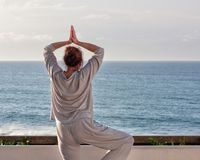 Pacific Ocean, woman exercise breathing on the terrace. Middle age woman standing on the terrace practicing Qigong and yoga exercises, view of the Pacific ocean Royalty Free Stock Photos