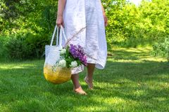 Middle age woman in white simple linen dress stays barefoot on the grass in beautiful garden and holds knitted white-yellow bag stock images