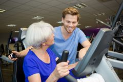 Middle age woman exercising with fitness instructor in gym Royalty Free Stock Photos