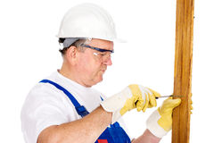 Middle age worker screwing nail in board Stock Photo