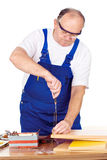 Middle age worker screwing nail in panel board Stock Photos