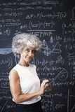Middle aged academic woman at blackboard smiling to camera royalty free stock photography