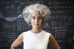 Middle aged academic woman standing in front of blackboard stock image