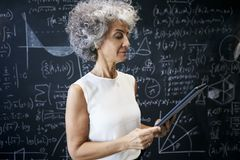 Middle aged academic woman working at blackboard royalty free stock photography