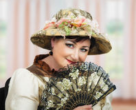 Middle aged actress posing in retro hat with fan Stock Images