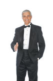 Middle aged Adult Male Wearing Tuxedo. Middle Aged Adult Male Wearing a Tuxedo arm extended for handshake isolated on white Stock Photo