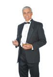 Middle aged Adult Male Wearing Tuxedo. Middle Aged Adult Male Wearing a Tuxedo and Holding a Lit Cigar and Whiskey Glass isolated on white Stock Photography
