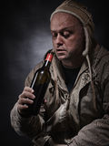 Middle aged alcoholic and wine bottle Stock Images