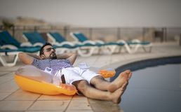 Middle aged arab man by a pool. Middle aged arab man enjoying his summer holiday by a pool stock photos
