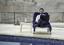 Middle aged arab man by a pool in his business attire Royalty Free Stock Photography