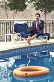 Middle aged arab man by a pool in his business attire Stock Photography