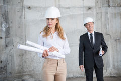 Middle aged architects in hardhats holding blueprints and working at construction site Stock Images