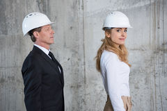 Middle aged architects in hardhats walking at construction site Stock Photography