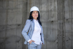 Middle aged asian businesswoman wearing hard hat and looking away stock photo