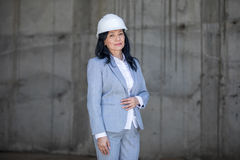 Middle aged asian businesswoman wearing hard hat and looking at camera stock photo