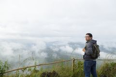 Man relax on mountain. Middle aged Asian man backpack relax and refresh on mountain background is a landscape of high mountains, white clouds and fog Royalty Free Stock Photography
