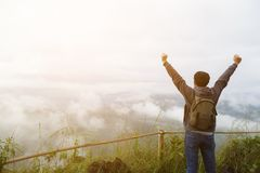 Man relax on mountain. Middle aged Asian man backpack relax and refresh on mountain background is a landscape of high mountains, white clouds and fog Stock Image