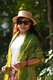 Middle aged Asian woman. In hat and sunglasses with leafy summer background stock photography