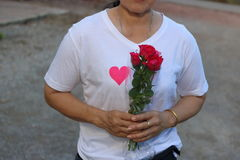 Middle aged asian woman is holding a beautiful bouquet of red roses. Love and romance Valentine`s day concept. Royalty Free Stock Photography
