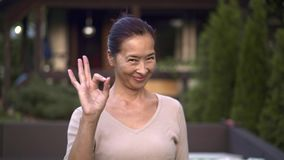 Middle aged asian woman showing ok sign outside