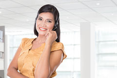 Middle aged Asian woman using a headset, smiling at the camera Stock Images
