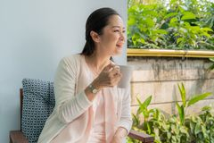 Middle-aged Asian women sit and sip coffee royalty free stock images