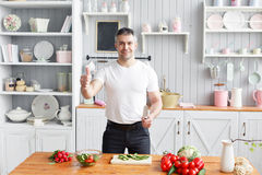 Middle-aged athlete, cuts vegetables salad of cucumber and tomato. Vegetarian food royalty free stock photo