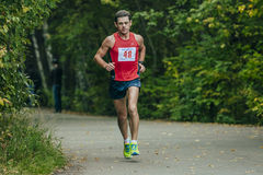 Middle-aged athlete runs through the Park Royalty Free Stock Photography