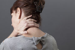 Middle aged with back or neck pain lady massaging herself Stock Image