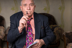 Middle Aged Bald Businessman Holding Pen and Notes. Close up Middle Aged Bald Businessman Holding Pen to Corner of his Mouth and Small Notes, Looking at the Royalty Free Stock Photo