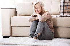 Middle aged barefoot woman sitting at the floor embracing her knees, near sofa at home, her head down, bored, troubled. Depression. Middle aged barefoot woman Stock Images